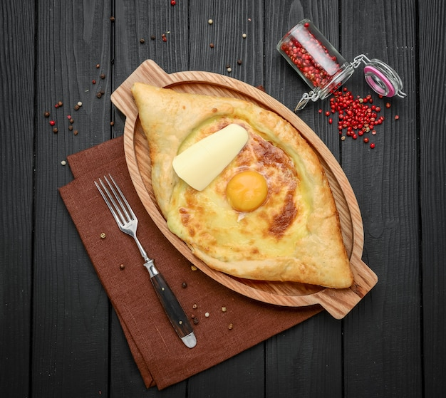 Hand mixing ingredients of adjarian khachapuri with fork in restaurant. open bread pie with cheese and egg yolk. yummy georgian cuisine. Premium Photo