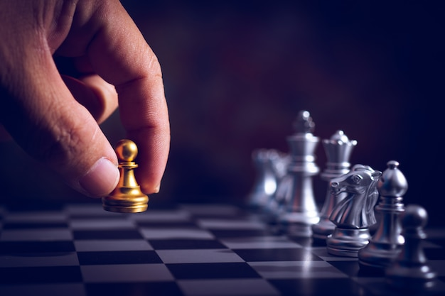 Hand move back rank of chess boad game to practice planing and stratagy, business thinking concept Premium Photo