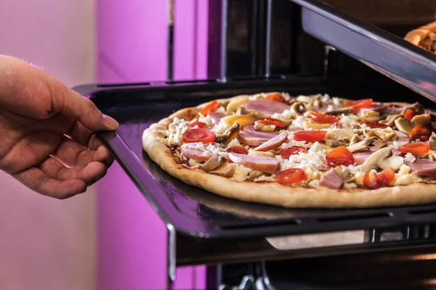 Hand moves the tray of pizza with mushrooms, ham and mozzarella Premium Photo