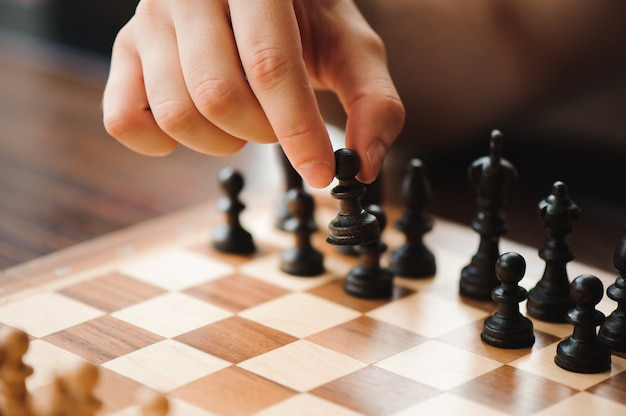 Hand moving chess figure in competition success play. Premium Photo