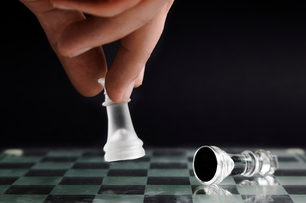 Hand moving transparent chess pieces Free Photo