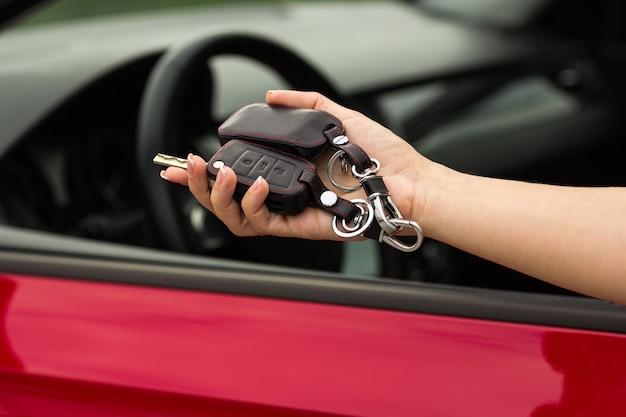 Hand Of A Girl With A Car Key In Hand On A Red Car Background Photo