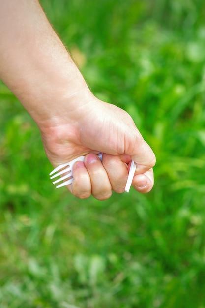 Рука маленькой девочки, держащей пластиковый мусор на зеленой траве в парке Premium Фотографии
