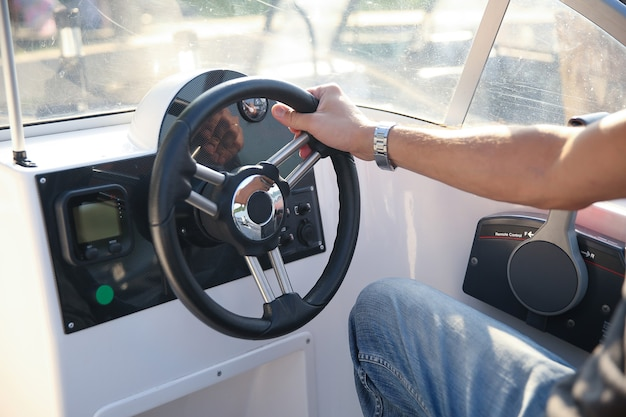 Рука человека на штурвале моторной лодки Premium Фотографии