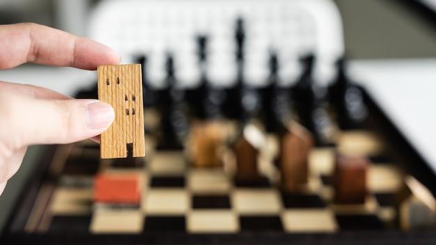 チェスゲームで建物や家のモデルを移動するビジネスマンの手 Premium写真