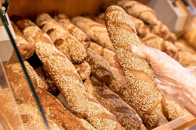 スーパーマーケットを訪問し、食品を購入しながらパンのディスプレイから新鮮なバゲットを取り、手袋をはめた女性の顧客の手 Premium写真