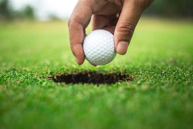 Рука гольфиста, держащего отверстие для мяча для гольфа Premium Фотографии