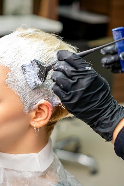 클라이언트 머리에 흰색 페인트를 적용하는 미용사의 손 프리미엄 사진