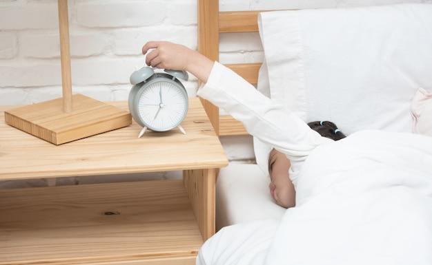 Рука маленького азиатского будильника касания девушки пока она кладя положила звенеть стопа часов. Premium Фотографии