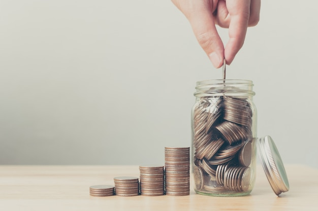 Hand of male or female putting coins in jar with money Premium Photo