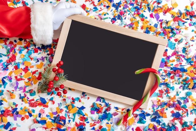 サンタクロースの手は、ショッピングボードで明るい紙吹雪の背景にギフトを保持しています。 Premium写真