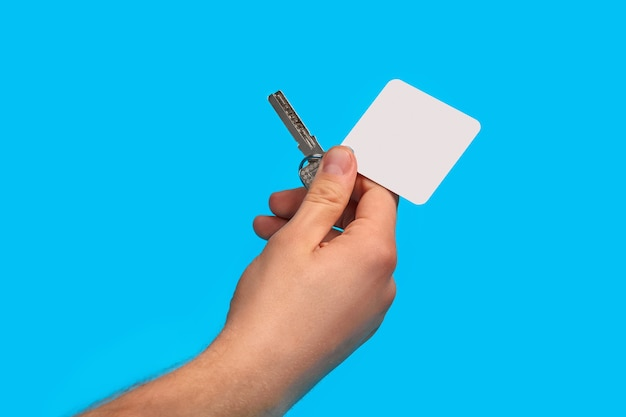 인식 할 수없는 남자의 손은 금속 링에 빈 흰색 사각형 플라스틱 열쇠 고리와 열쇠를 들고있다 프리미엄 사진