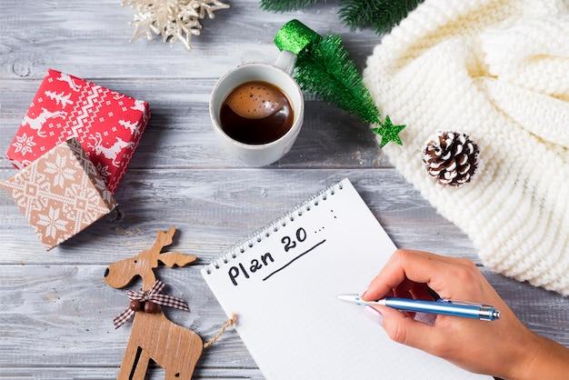 Рука женщины, писать на блокноте рождественские поздравления с чашкой чая, украшения на деревянные Premium Фотографии
