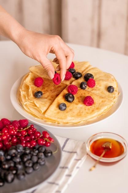 朝食を食べながら皿の上の自家製パンケーキの上から新鮮な熟したラズベリーを取る若い女性または主婦の手 Premium写真