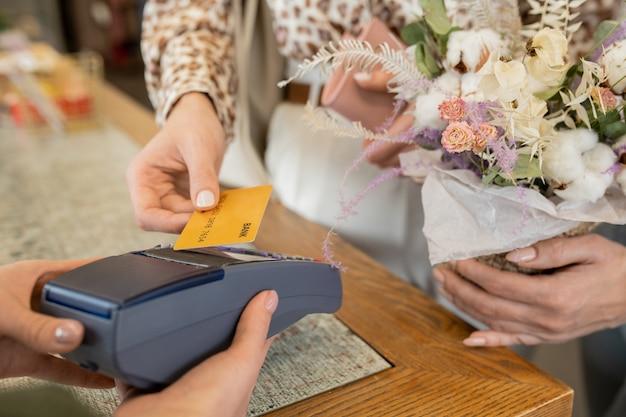 花屋で花の支払いをしながらカウンターの決済端末にクレジットカードを持っている花の花束を持つ若い女性の買い物客の手 Premium写真