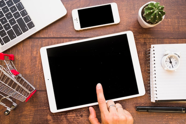 Рука на планшете возле смартфона, ноутбука и торговой тележки Бесплатные Фотографии