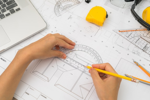 Hand over Construction plans with yellow helmet and drawing tool ...