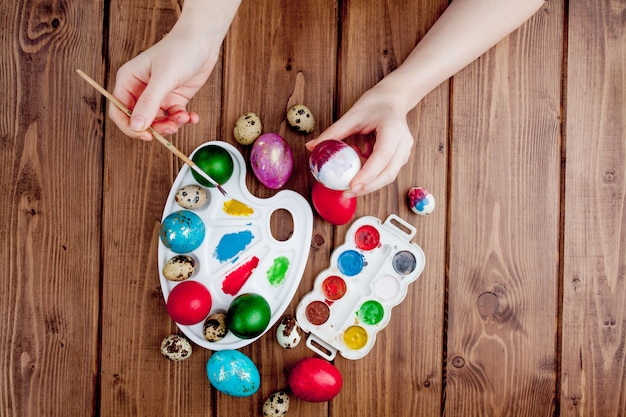 Hand painted easter eggs, paints and brushes on wooden background. preparation for the holiday. girls hands draw a pattern Premium Photo