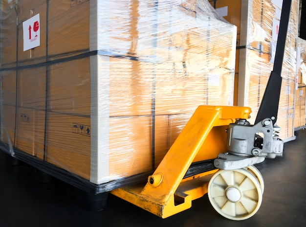 Hand pallet truck with cargo pallet. the shipment for transportation. Premium Photo