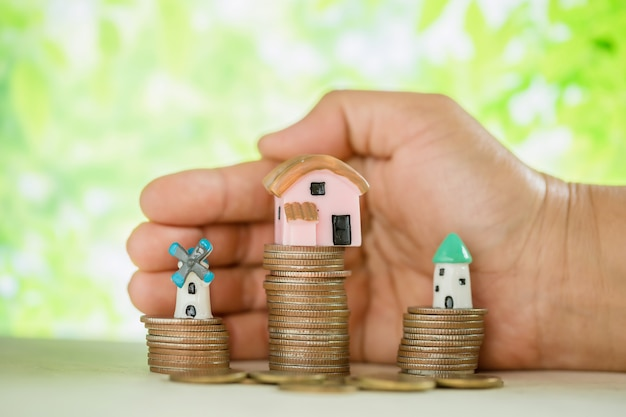 Hand pampered coins and small house model Free Photo