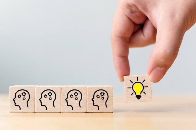 Hand pick wooden cube block with head human symbol and light bulb icon Premium Photo