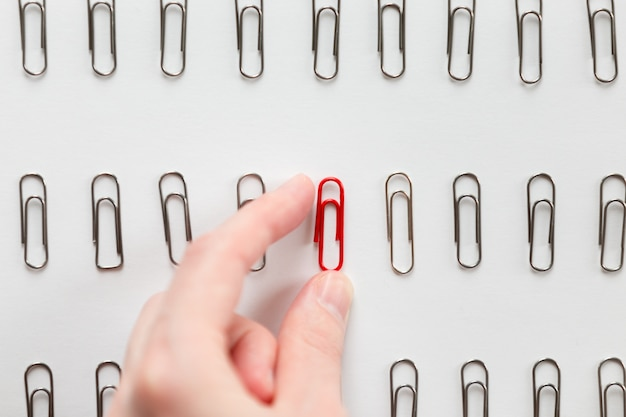 Hand picking among metal paperclips one red, different from others Free Photo