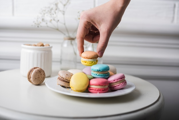 Hand picking up the macaroon from white plate kept on the white table Free Photo