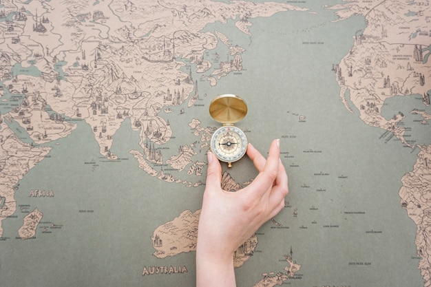 Hand placing a compass on a world map Free Photo