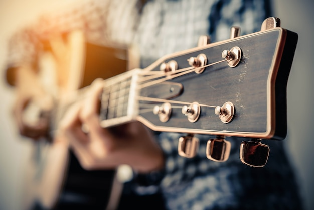 Hand play acoustic fingerstyle guitar. Premium Photo