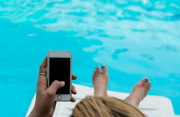 Hand play white smartphone at swimming pool.woman using her phone while sitting relax at p Premium Photo