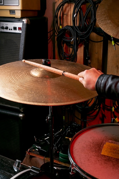 Hand playing on cymbal with stick Free Photo
