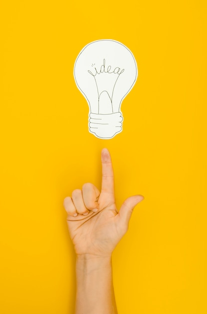 Hand pointing to a lighten bulb Free Photo