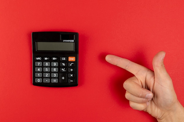 Hand pointing to a mini calculator Free Photo