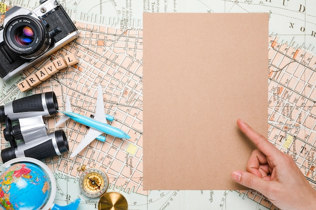 Hand pointing next to travel elements Free Photo