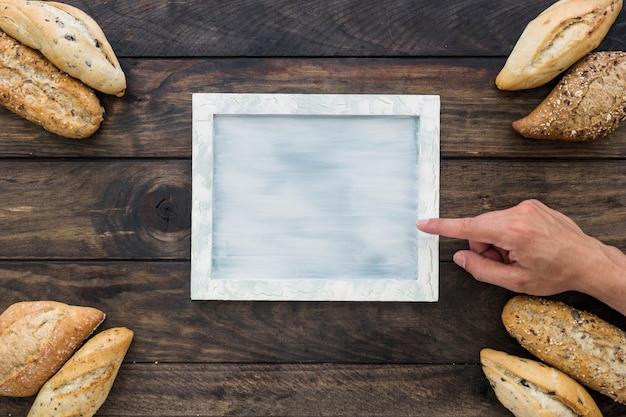 Mano che indica al vassoio vicino a pagnotte di pane Foto Gratuite
