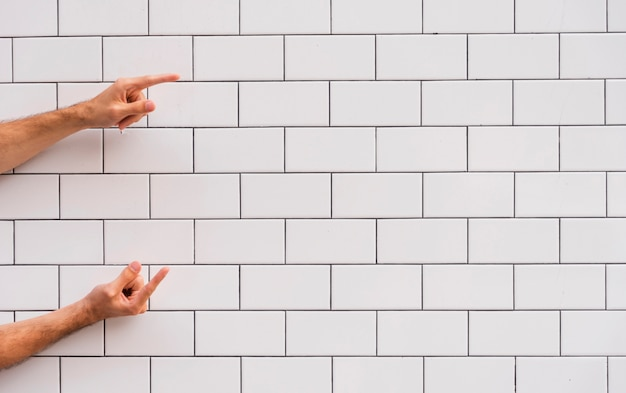 Hand pointing at white brick wall Free Photo