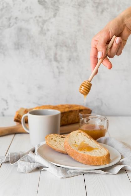 Рука наливает мед на ломтик хлеба Бесплатные Фотографии