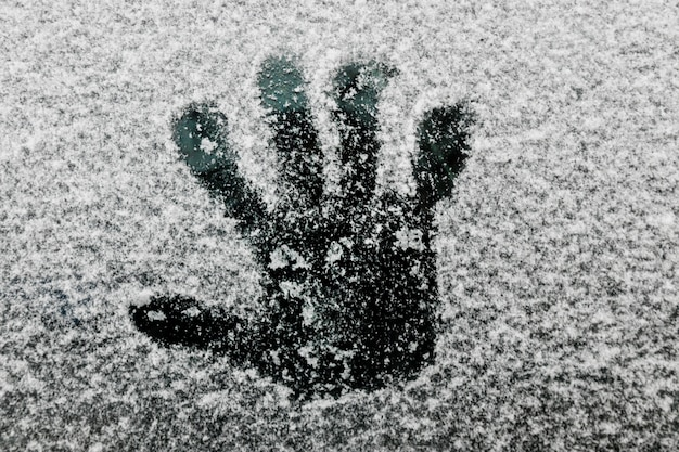 Hand print on glass in winter Free Photo