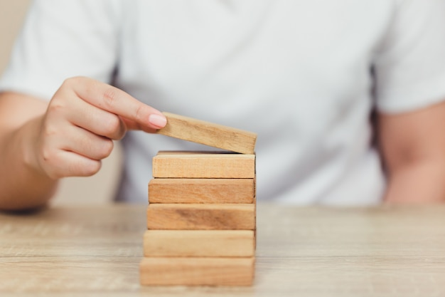 Hand Pulling Out Or Placing Wood Block On The Tower Plan And