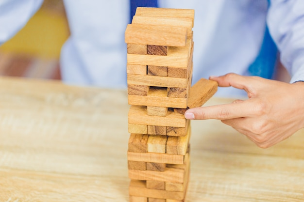 Hand pulling out or placing wood block on the tower,  plan and strategy in business Premium Photo