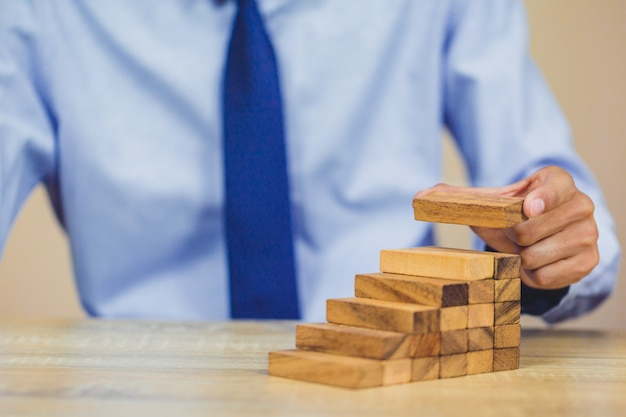 Hand pulling out or placing wood block on the tower. Premium Photo