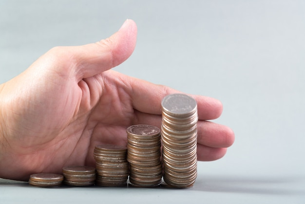 Hand pushing a pile of coins, column of coins falls Premium Photo