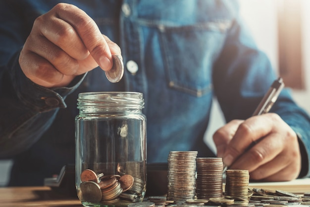 Hand puting coins into jug glass for saving money finance and accounting concept Premium Photo