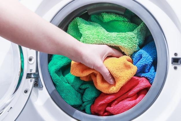 Hand and puts the laundry into the washing machine Premium Photo