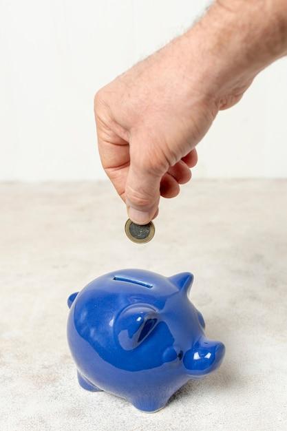 貯金箱にコインを入れて手 無料写真