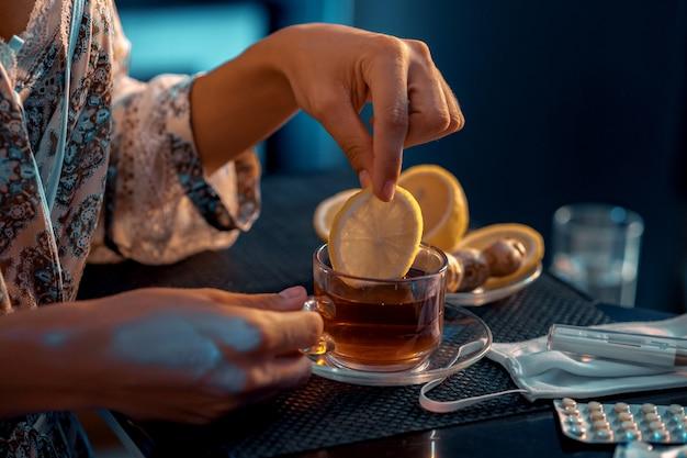 レモンのスライスをグラスに入れて手 Premium写真