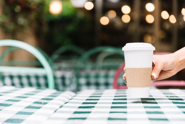 Hand putting coffee on a table Free Photo