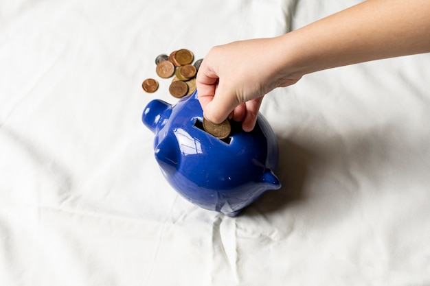 Hand putting coins in a piggy bank Premium Photo