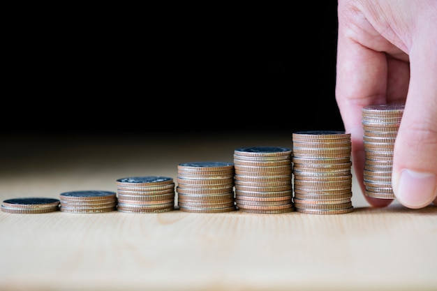 Hand putting coins stacking on black background which it is symbol for saving in the future and fund stock value investment. Premium Photo