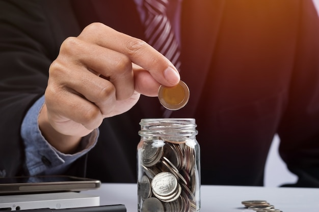 Hand putting mix coins and seed in clear bottle and copyspace, business investment growth concept. Free Photo